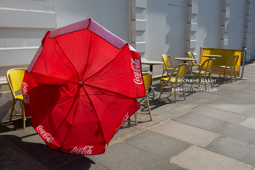 A blown-over red brolley and yellow seats at a cafe in Victoria, on 15th April 2019, in London, England.