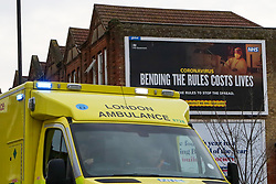 © Licensed to London News Pictures. 21/02/2021. London, UK. An ambulance responding to an emergency drives past the government's 'Bending The Rules Costs Lives' awareness publicity campaign poster displayed on the side of a property in north London. Prime Minister Boris Johnson will announce on Monday, 22 February the government's plans for relaxing Covid-19 restrictions in England. It is expected that families to be reunited, andschools will re-open on 8 March. Photo credit: Dinendra Haria/LNP