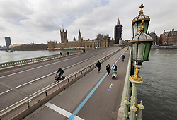 © Licensed to London News Pictures. 24/03/2021. London, UK. People cross a quiet Westminster Bridge on the anniversary of the announcement of the first lockdown on March 24th 2020. Traffic is still relatively light, but the pavements are marked with a blue line one way system for pedestrians to enable social distancing. Coronavirus restrictions are to be eased over the coming weeks as vaccinations near 30 million and infection rates and deaths continue to drop. Photo credit: Peter Macdiarmid/LNP