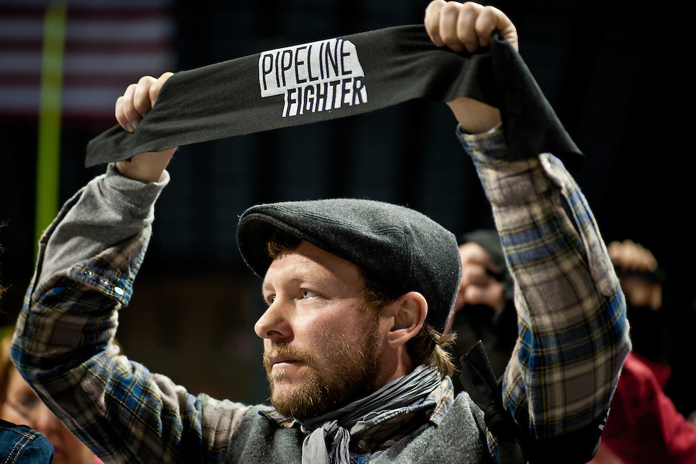 """Ben Gotschall holds a """"Pipeline Fighter"""" armband at the State Department hearing on the Keystone XL Pipeline Project in Grand Island."""