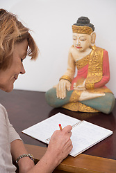 Senior woman writing in notebook, Buddha statue in the background, Munich, Bavaria, Germany