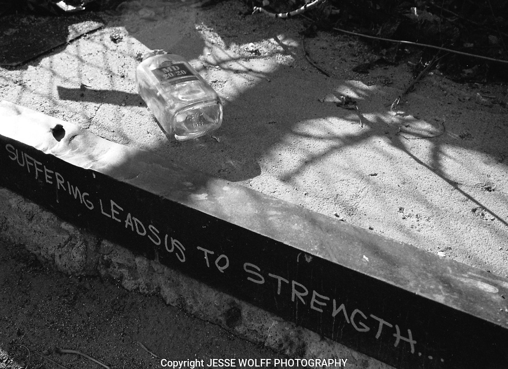 I found this inscription in an alley off of Broadway Avenue in Denver, Colorado.  None of it was staged.  The bottle was there.