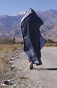 Bagram, Afghanistan. Woman walking along a road with red and white stones marking the fact there are landmines.