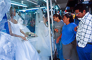19 JANUARY 2002, LEON, GUANAJUATO, MEXICO: A family looks at wedding dresses in a disaply window in a store in Leon, Guanajuato, Mexico. .PHOTO BY JACK KURTZ