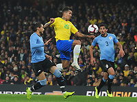 Football - 2018 / 2019 International Friendly - Brazil vs. Uruguay<br /> <br /> Roberto Firmino of Brazil out jumps Bruno Mendez and Martin Caceres of Uruguay, at The Emirates.<br /> <br /> COLORSPORT/ANDREW COWIE