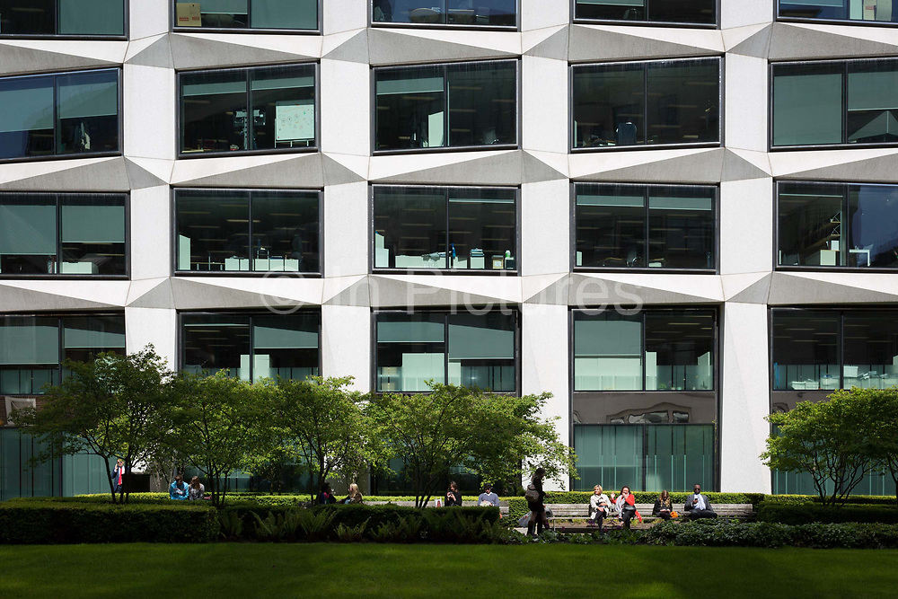City workers enjoy spring sunshine in a small green space outside corporate offices, the capitals financial district, on 19th April, in the City of London, England.