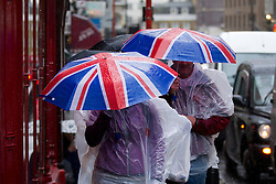 © Licensed to London News Pictures. 24/09/2012. LONDON, UK. Members of the public use Union Jack umbrellas and waterproof jackets in an attempt to stay dry in central London today (24/09/12). Rain and strong winds today hit the UK causing widespread disruption with gusts of up to 60mph predicted for the north of England and up to 80mm of rain predicted in some areas.. Photo credit: Matt Cetti-Roberts/LNP