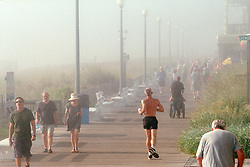 Joggers seem to disappear into the fog on the boardwalk in Rehoboth Beach, Del., Saturday, Aug. 17, 2019. (Photo by D. Ross Cameron)