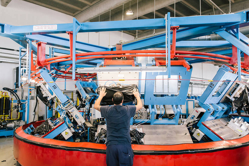"""OTTAVIANO, ITALY - 25 JULY 2019: A workers is seen here at a machine processing flexible polyurethan with film foaming and that produces fenders for Jeep Renegade, at Adler Group in Ottaviano, Italy, on July 25th 2019.<br /> <br /> Adler-Pelzer Group is an Italian manufacturing Group, and a worldwide leader in the design, development and manufacturing of components and systems for the transportation industry. Founded in 1956 in Ottaviano (Naples), today is the largest producer in Italy and the second in the world of systems for acoustic, thermal comfort and interior design for vehicles in the automotive, aerospace and railway industries. <br /> <br /> Italian manufacturer Adler-Pelzer Group had secured an order worth 2.6 million euros to make parts for military aircraft.That spelled 250 new jobs at its factory outside Naples, the heart of perpetually struggling southern Italy.<br /> """"It was a great opportunity,"""" says Adler-Pelzer Group chairman Paolo Scudieri.<br /> But early this year, alarmed by the intensifying political chaos gripping Italy, Mr. Scudieri's company shifted the order to a factory in Poland. He was disturbed by what he portrays as the anti-business proclivities of the populists suddenly running the country. He was concerned by the government's collision with the European Union over its spending plans.<br /> <br /> <br /> Italian companies are deferring expansions and limiting investment rather than risking cash in a time of uncertainty. The public debt remains monumental, running at more than 2 trillion euro ($2.24 trillion), or more than 130 percent of annual economic output. Banks are still stuffed with bad loans — albeit fewer than before — making them reluctant to lend. An economy that has not expanded over the past decade is this year widely expected to again produce no growth."""