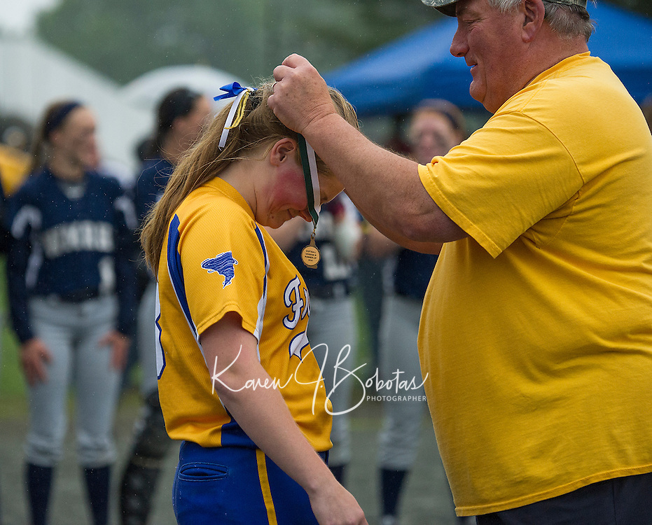 Meghan Johnston receives her runner up medal from Coach Dubois following the NHIAA Division III Softball state championship game with White Mountain at PSU Saturday afternoon.  (Karen Bobotas/for the Laconia Daily Sun)