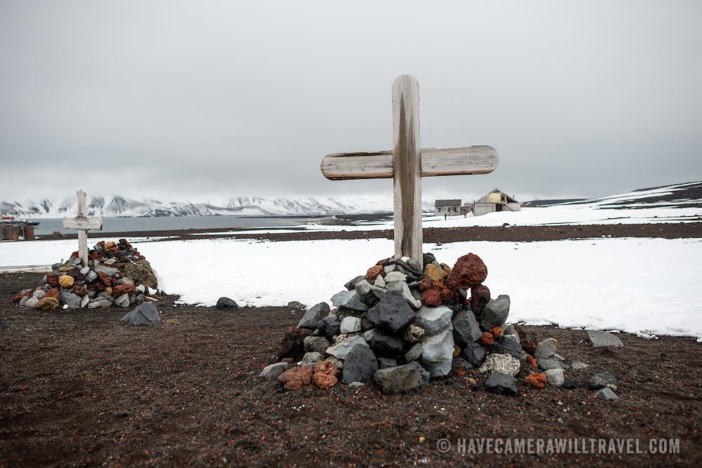 A small cemetery at the former whaling station at Whalers Bay, Deception Island. Deception Island, in the South Shetland Islands, is a caldera of a volcano and is comprised of volcanic rock.