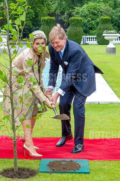 Koning Willem-Alexander en koningin Maxima tijdens het planten van een boom in het Presidentieel Paleis Aras an Uachtarain in Dublin, op dag 1 van het 3-daags staatsbezoek van het Nederlands Koningspaar aan Ierland.