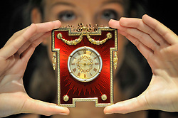 © Licensed to London News Pictures. 11/10/2017. London, UK. A model presents a Fabergé gold and enamel timepiece, 1908-13, (GBP120-180k) at a preview of a collection of English and continental silver and antique jewels from S.J. Phillips, one of London's oldest antique galleries.  The collection will be presented for sale by Sotheby's on 18 October in London. Photo credit : Stephen Chung/LNP
