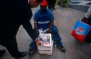 "Days after the September 11th 2001 attacks in New York and Washington DC, the US government had identified Osama Bin Laden as the head culprit of the terrorist action on America. Here, a businessman wearing a smart dark suit and polished loafers bends down to buy the latest copy of the New York Daily News from an African American vendor near Wall Street in the heart of New York's financial district. Bin Laden's demonic face is spread across the front page and the words ""Wanted: Dead or Alive"" tells Americans that their al-Qaeda evil-doer will be caught eventually, like a baddie rounded up by the Sheriff by the last scene of a Hollywood western.  ."