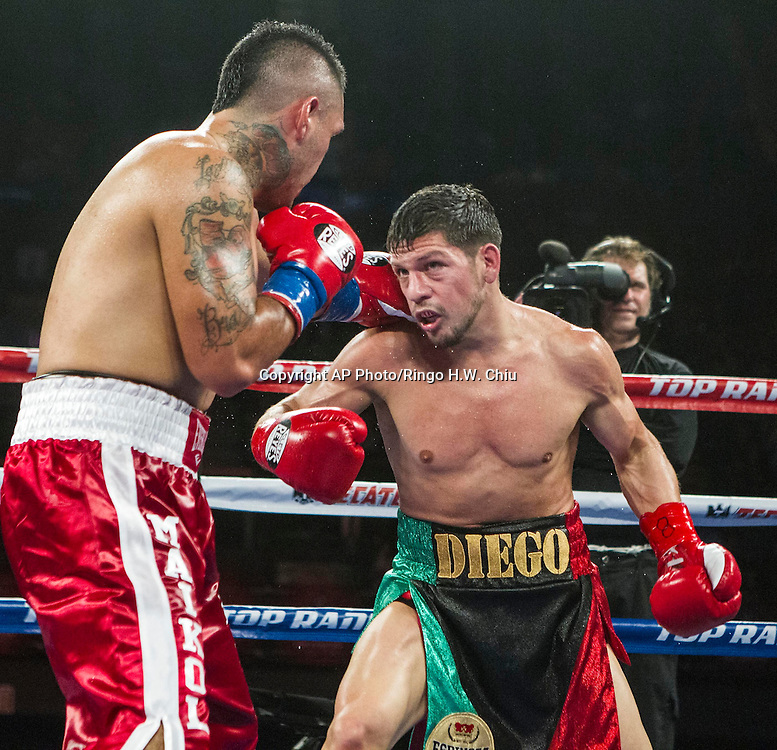 Diego Magdaleno, right, and Oscar Bravo, of Chile, exchange punches in a lightweight boxing match at the Forum in Inglewood, Calif., Saturday, May 17, 2014. .  (AP Photo/Ringo H.W. Chiu)