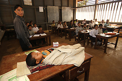 A teacher has brought his child to school and it sleeps on the desk while he takes a class Ban Dakduang, Dakcheung, near Sekong, Lao PDR