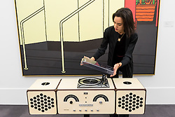 """© Licensed to London News Pictures. 01/11/2016. London, UK. A staff member examines """"Radio-Phonograph, Model no. RR126"""" by Achille and Pier Giacomo Catiglioni, est. GBP800-1,200. The first look of """"Bowie / Collector"""", artworks from the late David Bowie's personal art collection, ahead of their sale later this month at Sotheby's. Photo credit : Stephen Chung/LNP"""