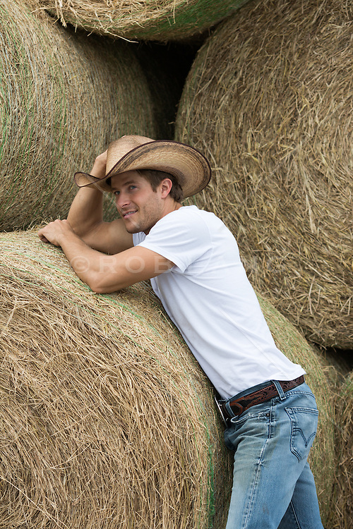 cute cowboy leaning on bales of hay
