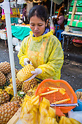 09 OCTOBER 2012 - BANGKOK, THAILAND:  A pineapple vendor cuts fresh pineapple at her cart in front of the Bangkok Flower Market. The Bangkok Flower Market (Pak Klong Talad) is the biggest wholesale and retail fresh flower market in Bangkok. It is also one of the largest fresh fruit and produce markets in the city. The market is located in the old part of the city, south of Wat Po (Temple of the Reclining Buddha) and the Grand Palace.    PHOTO BY JACK KURTZ
