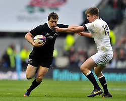 Ben Smith (New Zealand) looks to fend Owen Farrell (England) - Photo mandatory by-line: Patrick Khachfe/JMP - Tel: Mobile: 07966 386802 16/11/2013 - SPORT - RUGBY UNION -  Twickenham Stadium, London - England v New Zealand - QBE Autumn Internationals.