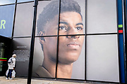 A woman of colour reads a caption beneath the large billboard, a portrait of English football player, Marcus Rashford, outside the Strand branch of Coutts Bank, on 14th October, 2021, in Westminster, London, England. Marcus Rashford has recently been awarded an honourary degree by The University of Manchester in recognition of his political campaigning on behalf of the underprivilged in particular, of school meals and his philanthropy. He currently plays for Manchester United and is in the English national team. He has also been the victim of online racial abuse.