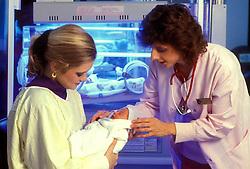 Stock photo of a nurse holding a newborn baby
