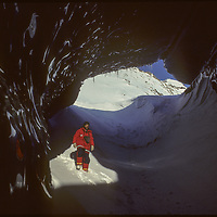 Glaciologists descend into opening of long, polar sub-glacial river cave.