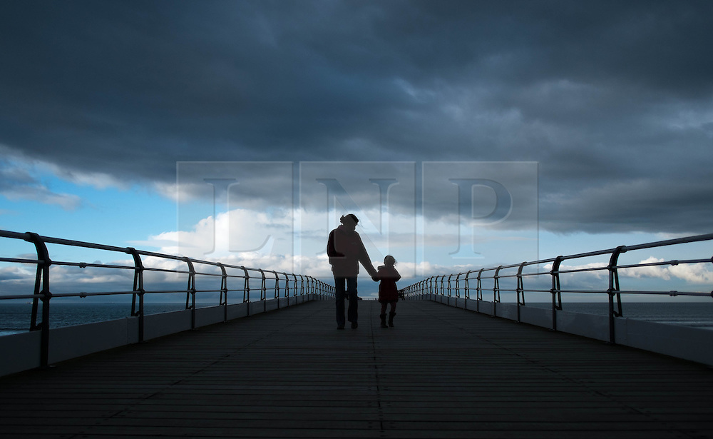 © Licensed to London News Pictures. 07/04/2014<br /> <br /> Saltburn, United Kingdom<br /> <br /> A woman and her daughter walk along the pier as dark storm clouds form over Saltburn by the Sea in Cleveland.<br /> <br /> Photo credit : Ian Forsyth/LNP