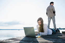 Woman wooden jetty working laptop computer