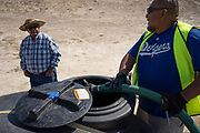 CB Barton fills his water tank while speaking to an elder at a well in Coyote Canyon Chapter in the Navajo Nation near Gallup, New Mexico.