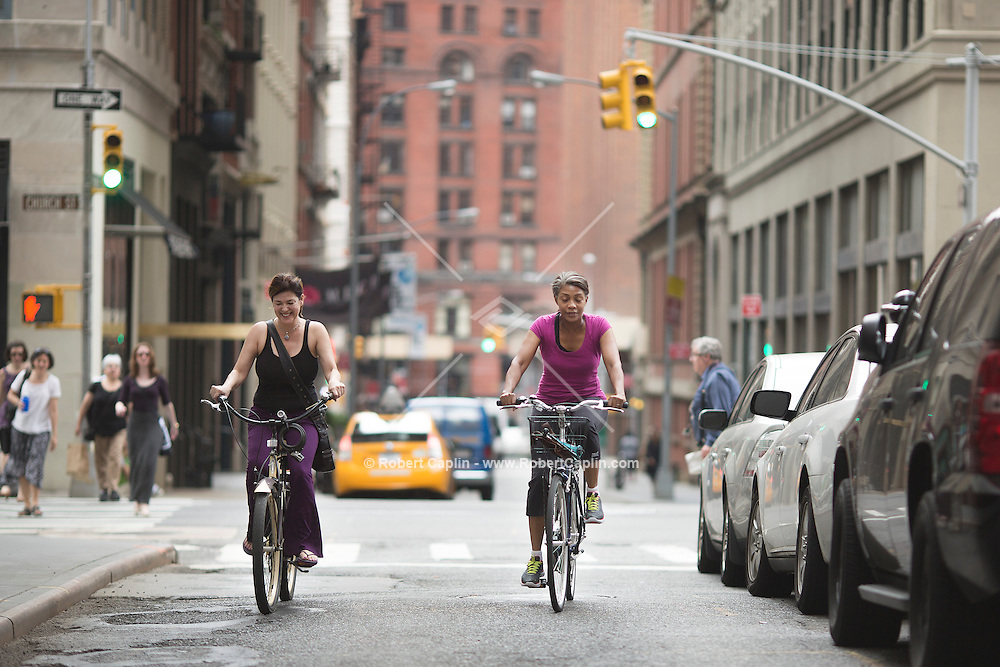 Penelope Crabtree, left (not on rental bike), who lives in Tribecca Towers and her friend Genevieve Samuel use a new private bike share program that Related Real Estate is launching at ten of its properties in NYC. Each property has between 2-4 bikes, operated by Zagster (a bike share company), that are available to residents of the building. It's the latest in a long line of amenities designed to make rentals more appealing. <br /> <br /> (Photo by Robert Caplin)