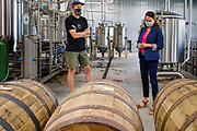 """22 JULY 2020 - AMES, IOWA: ELLIOT THOMPSON, owner of Alluvial Brewing, left, talks to THERESA GREENFIELD, about the barrels he uses in his brewery during a visit by Greenfield to Alluvial Brewing in Ames, IA. Greenfield, a Democrat, is running for the US Senate against incumbent Republican Senator Joni Ernst. Recent polls have Greenfield slightly ahead of or statistically tied with Ernst, who is closely allied with President Donald Trump. Although Greenfield is not doing much in person campaigning with big events, she is meeting with business people across the state of Iowa to promote her """"Small Towns, Bigger Paychecks"""" economic program.          PHOTO BY JACK KURTZ"""