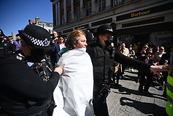 © Licensed to London News Pictures. 17/04/2021. Windsor, UK. A female protester is detained by police after streaking outside Windsor Castle, in Windsor, Berkshire, during the funeral of Prince Philip, The Duke of Edinburgh. Prince Philip, the Consort of the longest reigning English monarch in history, Queen Elizabeth II, died on 9 April 2021, two months before his 100th birthday. Photo credit: Ben Cawthra/LNP