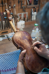 Close-up of violin maker painting violin in workshop
