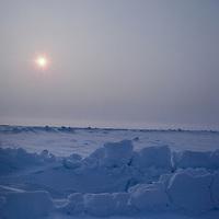 NORTH POLE. Midnight sun circles pressure ridges on sea ice drifting over Arctic Ocean at the Pole.