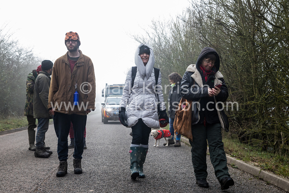 Denham, UK. 6 February, 2020. Environmental activists from Save the Colne Valley, Stop HS2 and Extinction Rebellion walk at a snail's pace along a road in order to block a security vehicle and truck delivering fencing and other supplies to be used for works associated with the HS2 high-speed rail link close to the river Colne at Denham Ford. Works planned in the immediate vicinity include the felling of trees and the construction of a Bailey bridge, compounds and fencing, some of which in a wetland nature reserve forming part of a Site of Metropolitan Importance for Nature Conservation (SMI).