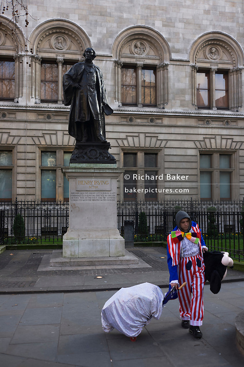Statue for Sir Henry Irving and an off-duty clown pulling his act possessions.