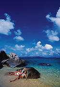 A family of four relaxes on large rocks that are scattered across a British Virgin Islands beach