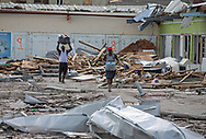 in an area called The Mudd, in Marsh Harbour, Abaco, men scavenge through a storm-wrecked store on Thursday, September 5, 2019. Hurricane Dorian destroyed large parts of Abaco Island as it passed through the Bahamas.