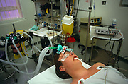 We are looking into the face of a young unidentified male patient before his wisdom tooth extraction procedure at the famous St. Bartholomews (Barts) Hospital in London, England. His eyelids have been taped shut, lying unconscious on his back with his head supported, prepped for this brief operation. Surrounding him is various medical equipment including anaesthetic gas that is fed through his nose by plastic tubes. it is spotlessly clean in this operating room, carefully, avoiding infection or bacterial problems like MRSA. Barts is Britain's oldest hospital – founded in 1123 - and boasts a progressive policy of encouraging day-surgery for out-patients allowing patients to return home soon after their minor operations.