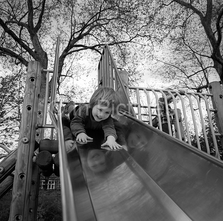 With hands outstretched and a nervous smile on her face, a 3 year-old goes head first down a slide in her local park in south London. The gradient helps the girl on her downward journey as the tentatively slides down with her fingers feeling the polished surface, her smiling, confident face reflected on the three sides of the slide's metal. Tall London plane trees rise above in this public London space.