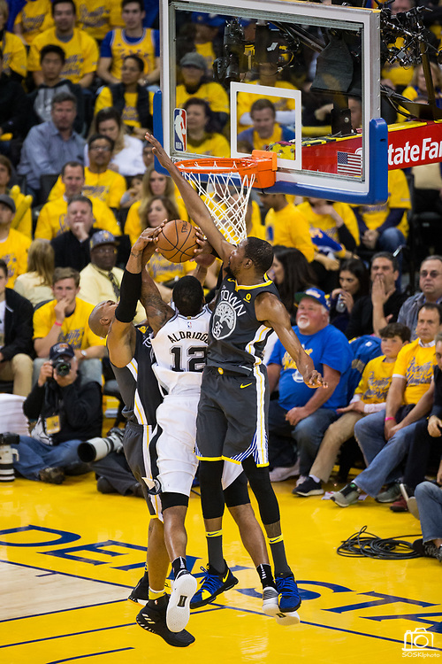Golden State Warriors forward David West (3) and Golden State Warriors forward Kevin Durant (35) block a shot by San Antonio Spurs forward LaMarcus Aldridge (12) during Game 2 of the Western Conference Quarterfinals at Oracle Arena in Oakland, Calif., on April 16, 2018. (Stan Olszewski/Special to S.F. Examiner)