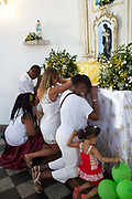 People showing their devotion to Sao Lazaro at an altar. Often the lines between Candomble and Catholicism are blurred. This is especially true with the Sao Lazaro event in late January in Salvador, Bahia, Brazil, the city which is known as the home of Candomble. Sao Lazaro represents healing and the sick.