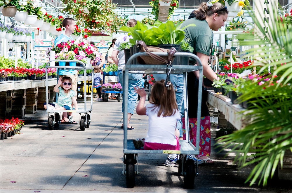 Matt Dixon   The Flint Journal..Joslynn Lyons (left), 3, of Swartz Creek waves to her new friend Brookelyn Phillips, 4, of Goodrich while the two shopped with family members at Wojo's Garden Splendors in Davison Township Sunday afternoon. Mother's Day is one of the busiest days of the year for the store.