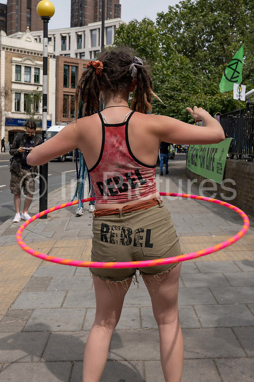 Extinction Rebellion campaigner Momo, Germany, hula hooping outside Waterloo Millennium Green, used as a temporary campsite during a week of climate change actions across the country on the 17th July 2019 in London in the United Kingdom. Extinction Rebellion are a socio-political movement using civil disobedience and nonviolent resistance to protest against climate breakdown, biodiversity loss, and the risk of social and ecological collapse.