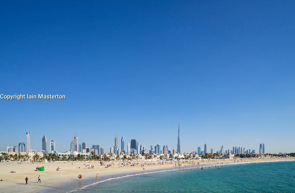 Daytime view of Jumeira Open Beach with tourists and skyline of skyscrapers in Dubai United Arab Emirates