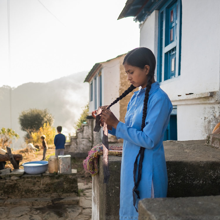 An indian girl does her hair before walking to school.