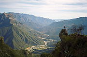 Hikers look down over the Copper Canyon (Barrancas del Cobre) and the village of Urique, Chihuahua, Mexico.