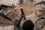 Workers are manually crushing raw stones containing gold, and other metals like lead, in an artisanal gold processing site near Bagega, pop. 9000, a large village affected by lead poisoning due to the unsafe techniques employed for extracting gold, in Zamfara State, Nigeria. The contamination is caused by ingestion and breathing of lead particles released in the steps to isolate the gold from other metals. This type of lead is soluble in stomach acid and children under-5 are most affected, as they tend to ingest more through their hands by touching the ground, and are developing symptoms often leading to death or serious disabilities.