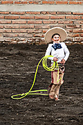 Eight-year-old Juan Franco, from the legendary Franco family of Charro champions proudly struts around the arena after successfully roping a wild mare during a practice session in the Jalisco Highlands town of Capilla de Guadalupe, Mexico. The roping event is called Manganas a Pie or Roping on Foot and involves a charro on foot roping a wild mare by its front legs to cause it to fall and roll once. The wild mare is chased around the ring by three mounted charros.
